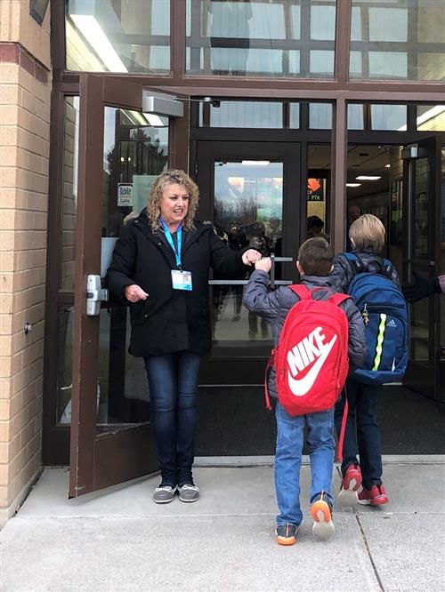 a volunteer welcomes students to school